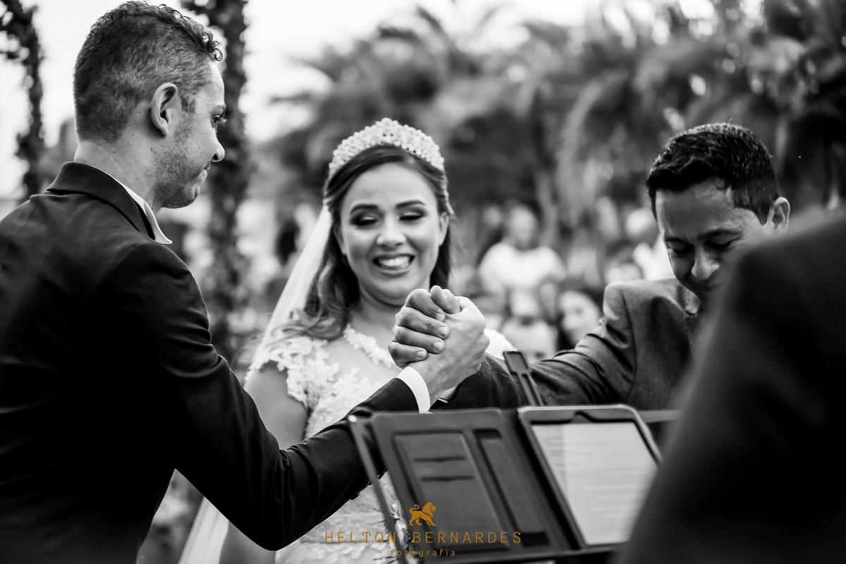 Aperto de mão do pai da noiva e o noivo,ao fundo a felicidade dela!