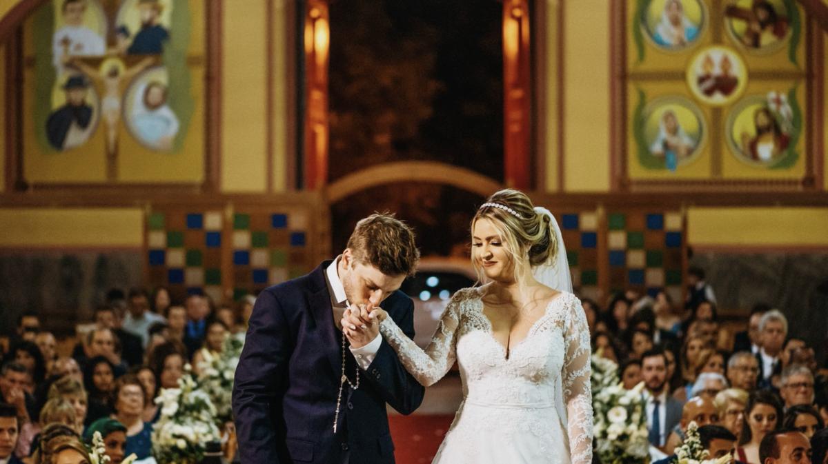 noivo beijando mão da noiva em igreja