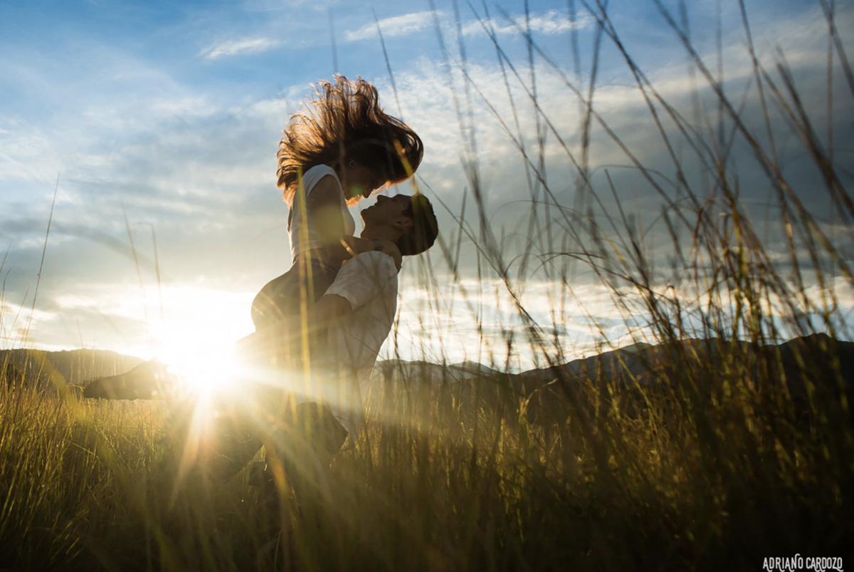 ensaio pré-wedding de casal em campo no por do sol