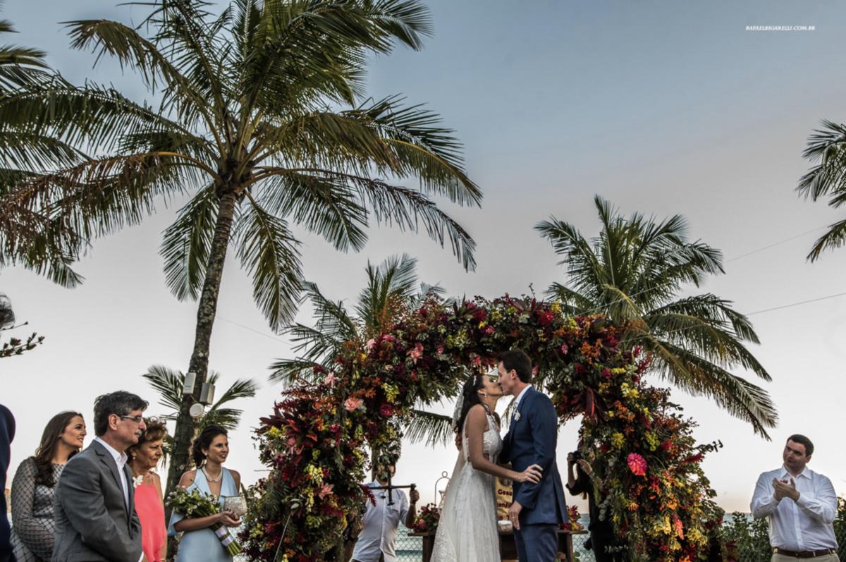 casal se beijando na frente de arcos de flores em decoração em casamento na praia em maresias sp fotógrafo rafael bigarelli
