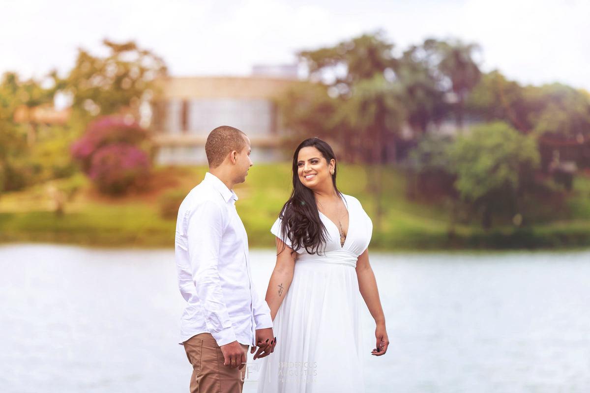Pré Casamento do Guilherme e Renata de mãos dadas tendo fundo os trações do belo projeto arquitetônico do Museu de Arte da Pampulha do mestre Oscar Niemeyer