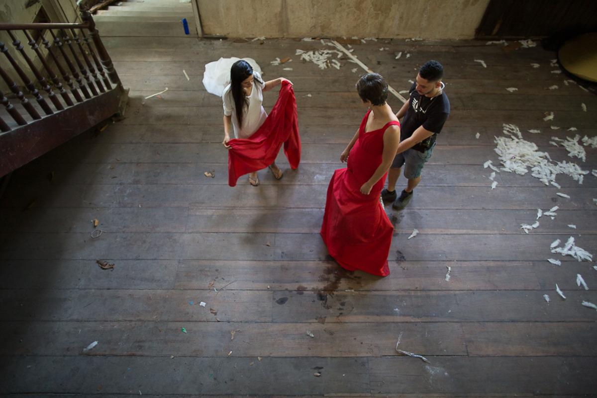 Foto de modelo com vestido vermelho e pessoas auxiliando na montagem da saia do vestido.