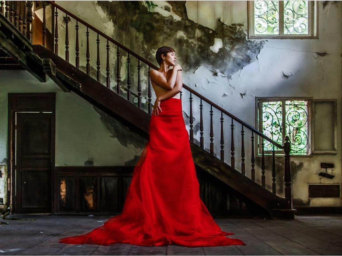 Mulher de vestido vermelho longo com rosto para o lado.