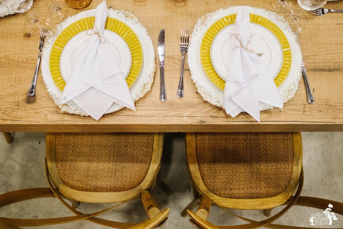 mesa dos noivos, com cadeira de madeira, prato amarelo e sousplat rústico para decoração boho chic, tipo DIY, com guardanapo amarrado com barbante de juta