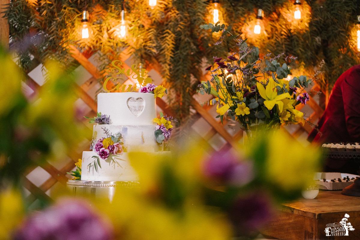 Bolo de casamento em decoração DIY com flores amarelas, roxas e folhagem verde, tudo rústico com madeira