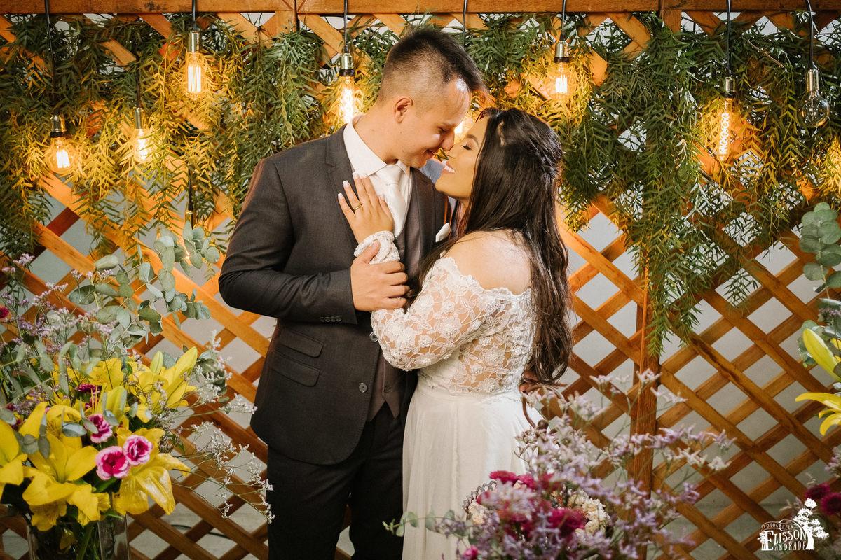 Casal abraçado em frente à decoração DIY com flores amarelas, roxas e folhagem verde, tudo rústico com madeira