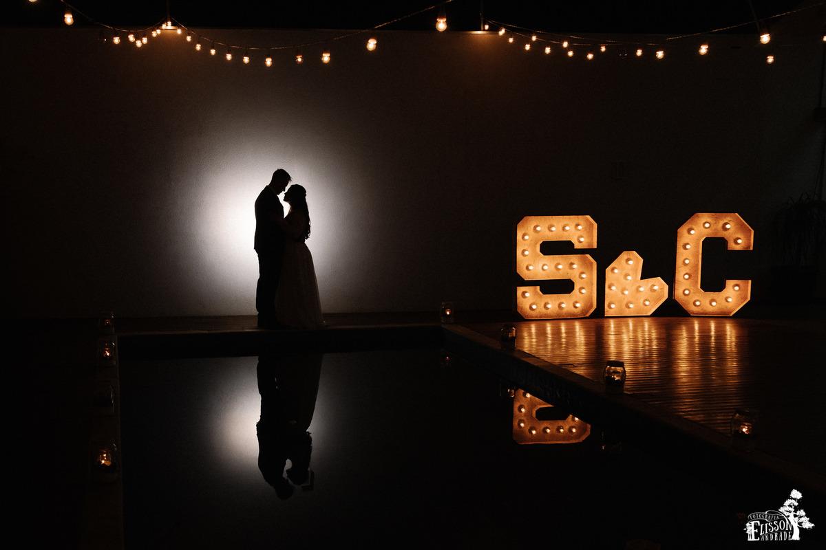 Foto de casal abraçado em silhueta junto com iniciais luminosas grandes