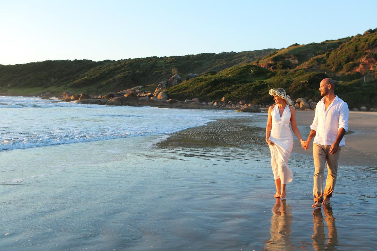 fotografia-praia-de-garopaba-praia-do-rosa-santa-catarina-fotografo-fabio-martins-fotografia-porto-alegre-casal-andando-na-beira-da-praia-noiva-com-coroa-branca-de-flores-naturais-noivo-segurando-a-mao-da-noiva-fotografia