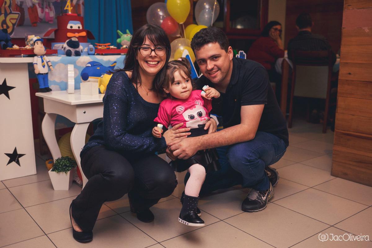 pais e filha posando em frente a mesa do bolo aniversário super wings