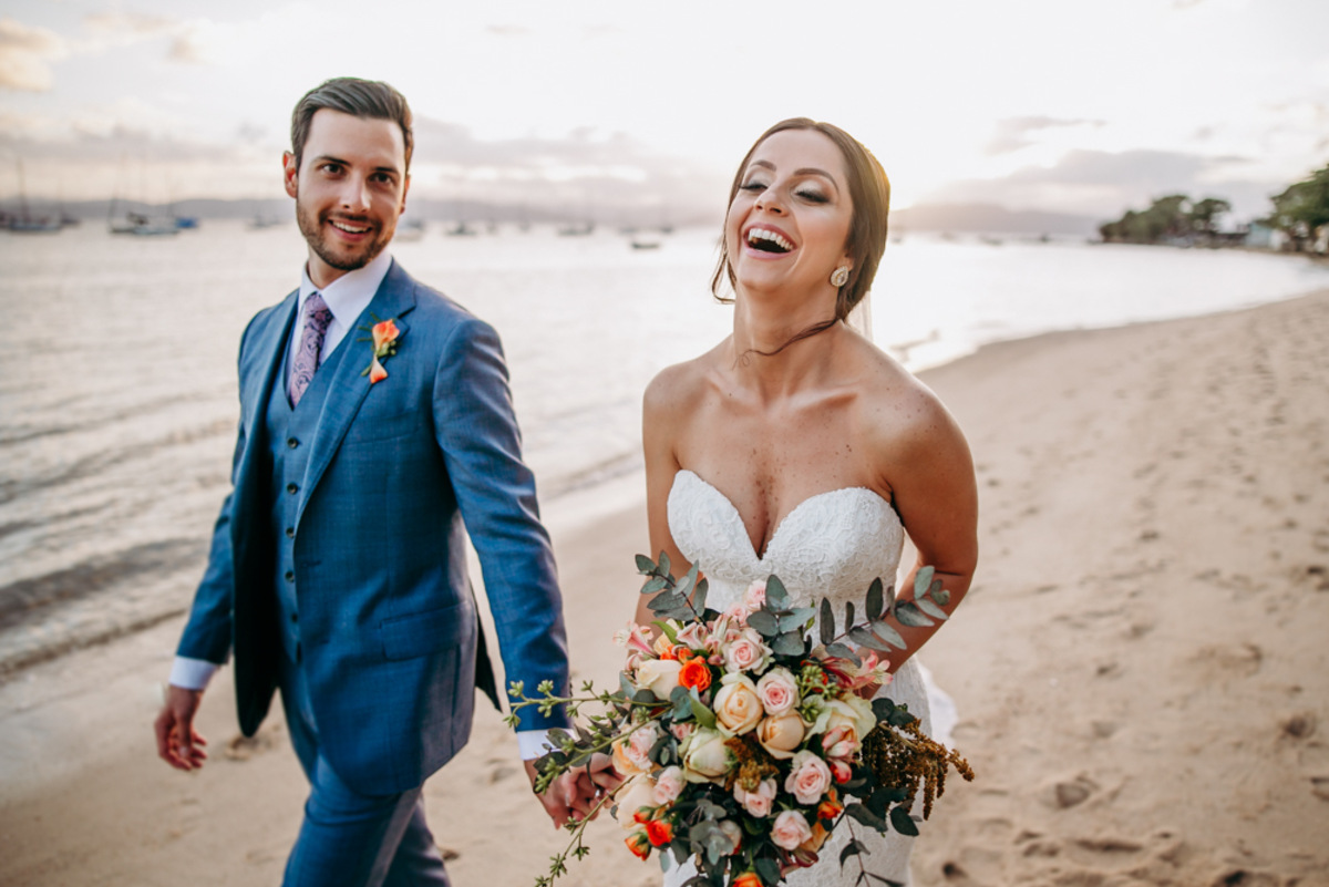 casal caminhando na praia com bouquet de flores