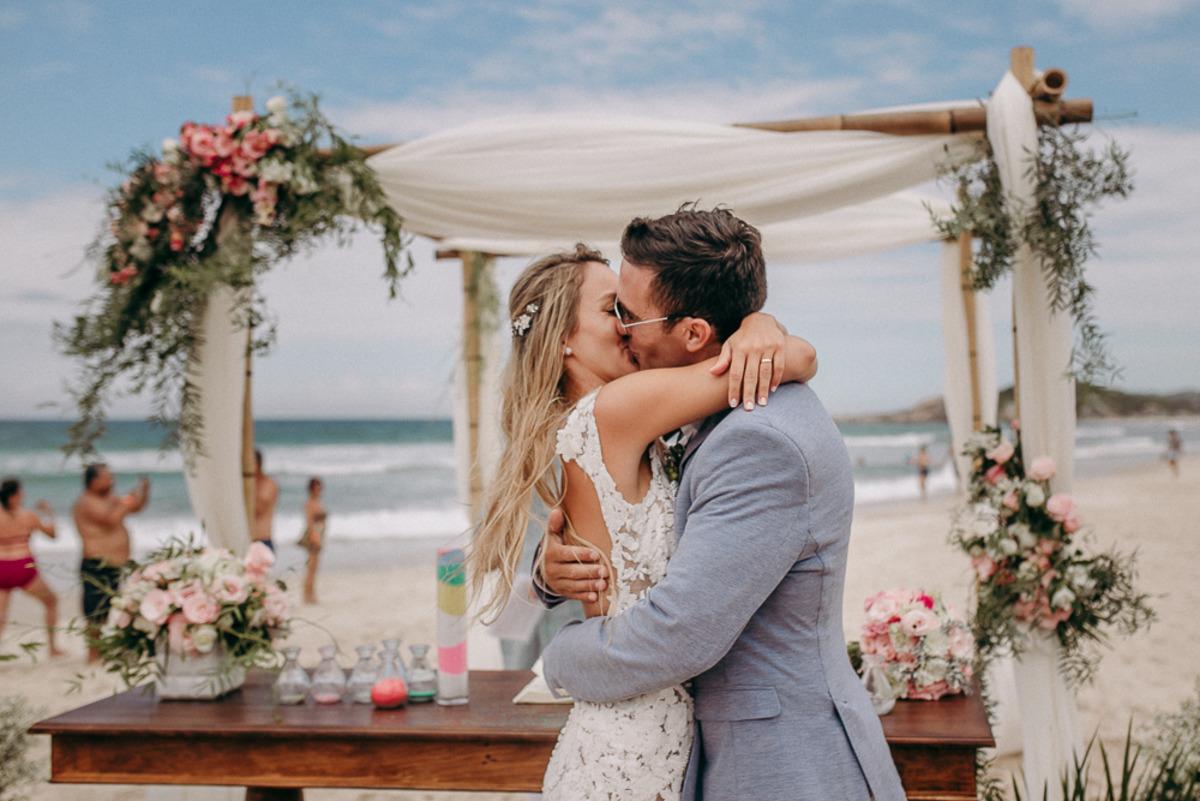 casal se beijando em casamento na praia