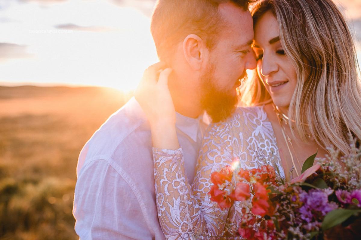 casal com flores em pôr do sol