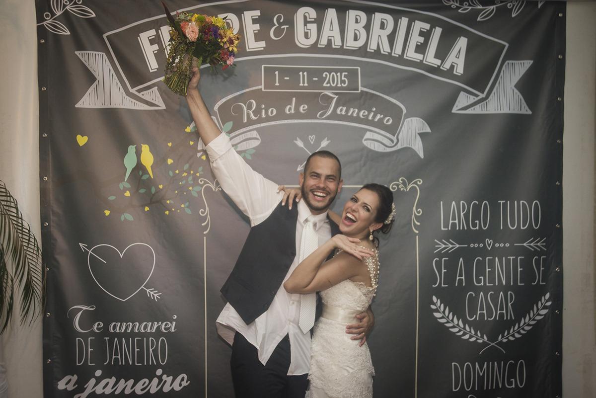 casal de noivos comemorando na frente de um banner com dizeres sobre o casamento