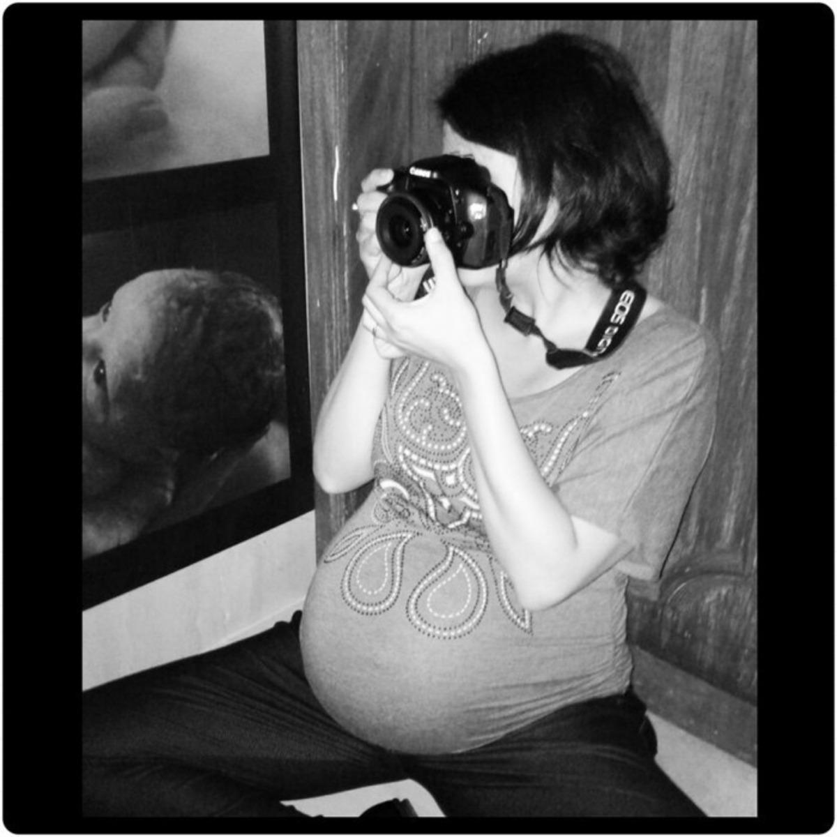 Mulher gestante sentada fotografando. Foto em preto e branco