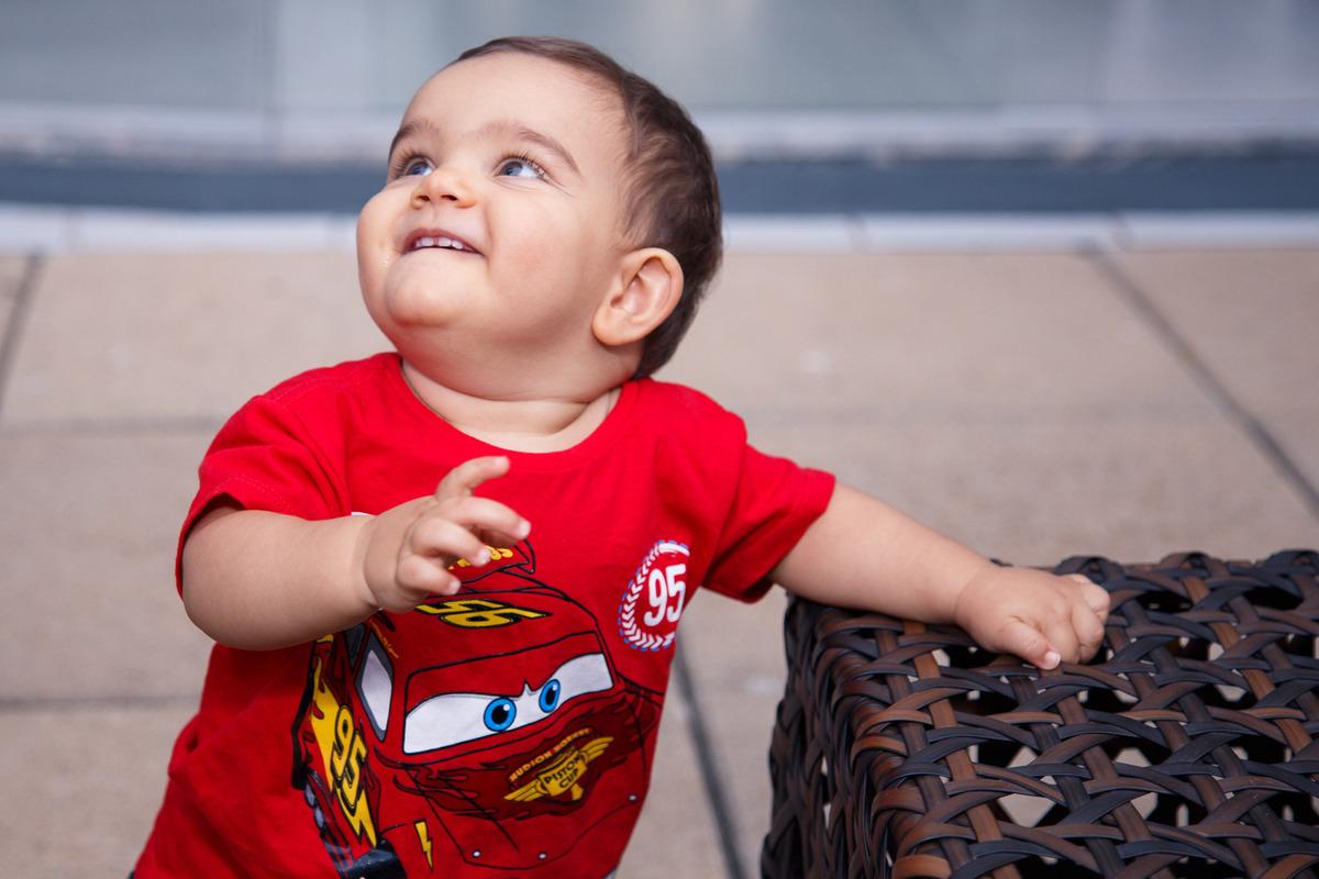 Bebê de pé apoiado em um banco de vime olhando para cima, com um sorriso mostrando os dentinhos de cima que estão nascendo.