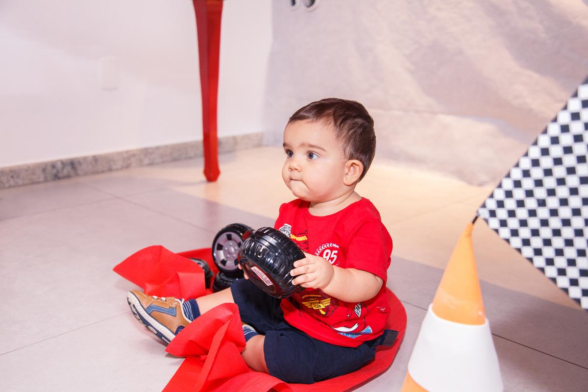 Criança brincando no chão com carrinhos durante seu aniversário de 1 ano no tema Carros.