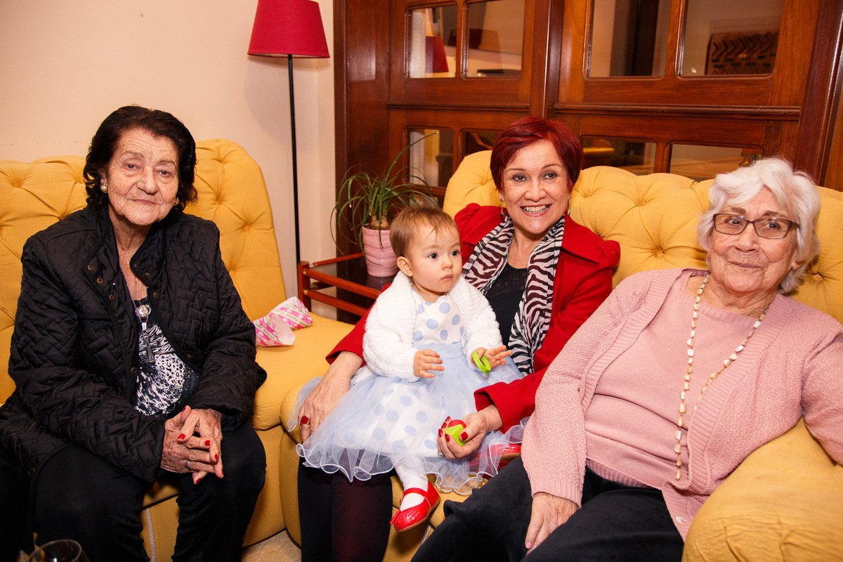Bebê em seu aniversário de um ano sentada no colo da avó junto de suas duas bisavós.