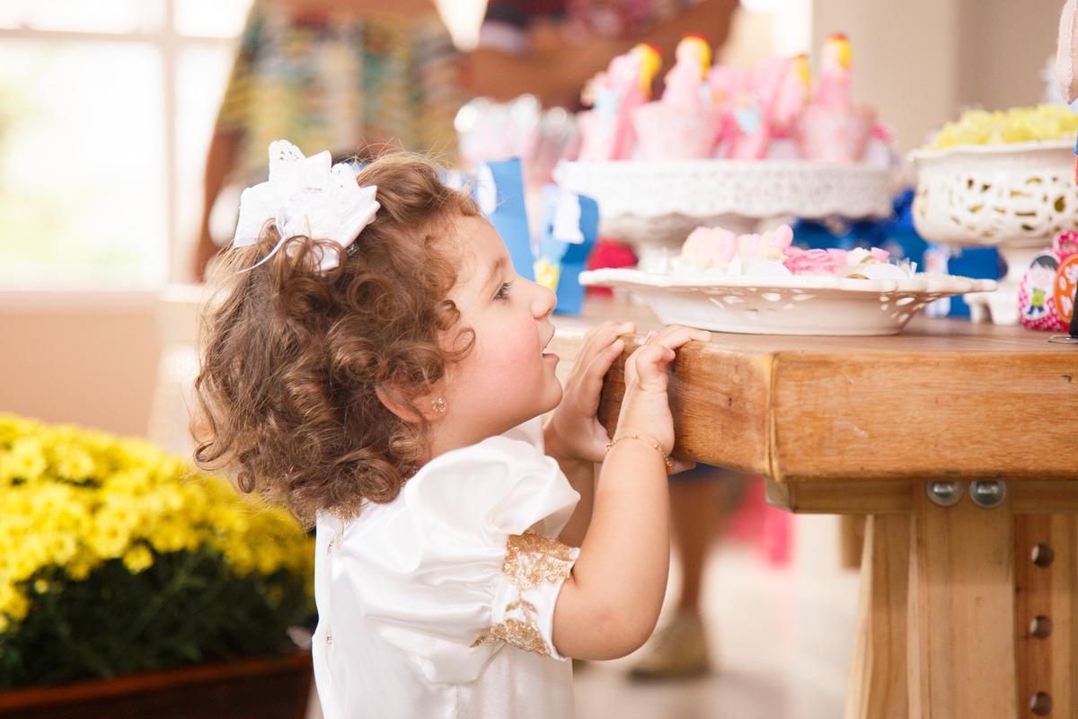 Criança de 2 anos em seu aniversário, na ponta dos pés olhando por cima da mesa do bolo.