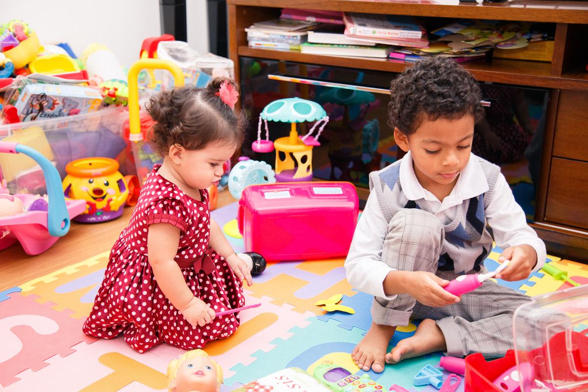 Duas crianças brincando no quarto de brinquedo durante um aniversário infantil intimista.