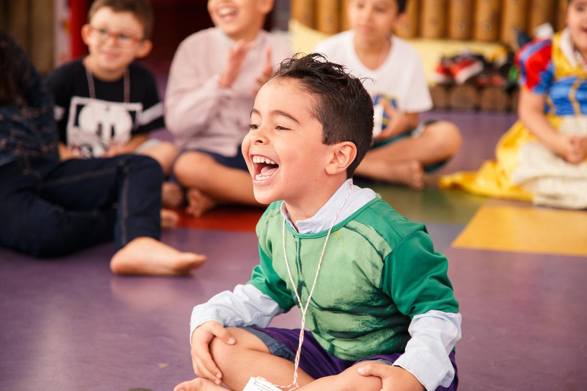 Criança sentada no centro de uma roda brincando em seu aniversário, com as mãos no joelho dando uma gargalhada.