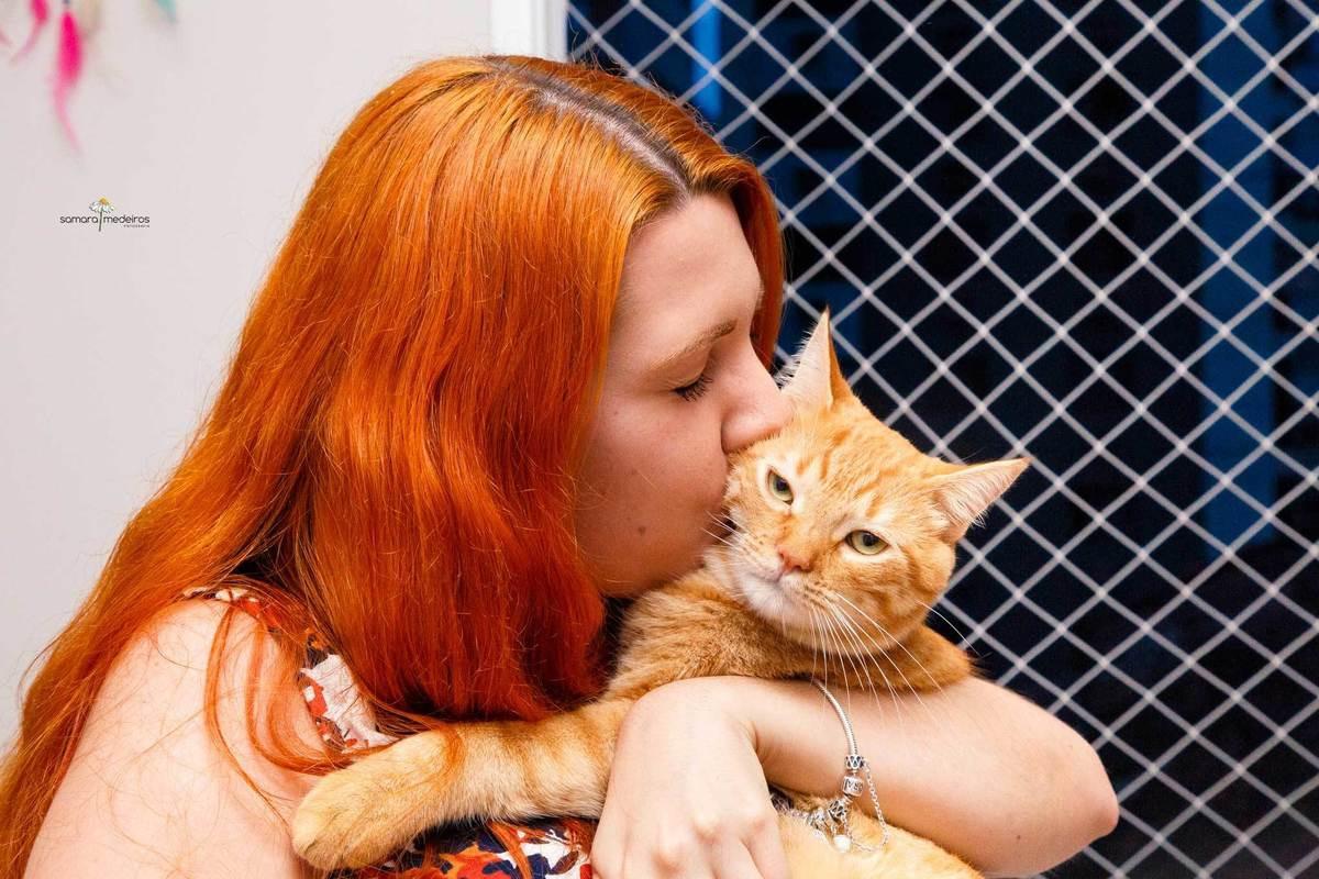 Tutora dando um beijo em seu gato, durante um ensaio pet em sua casa em Belo Horizonte.