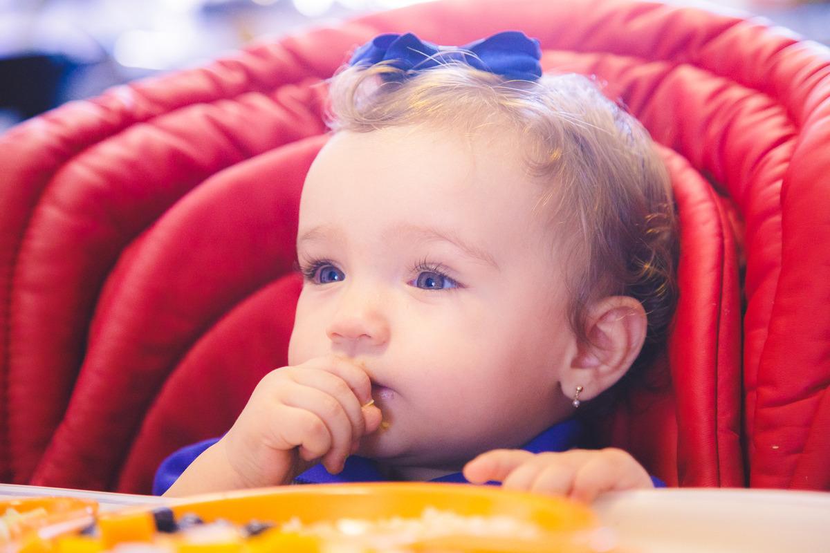 Bebê sentada em sua cadeirinha comendo papinha com a mão.