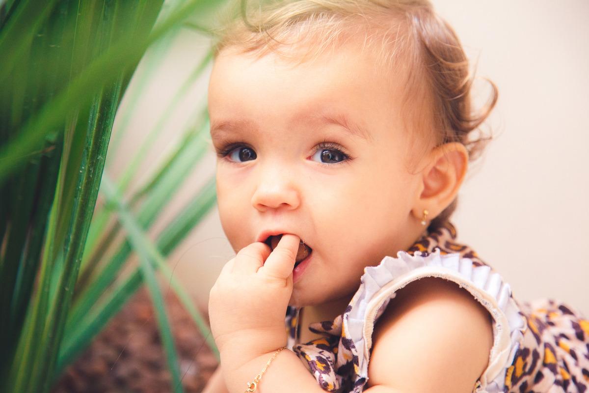 Bebê com dente coçando colocando um objeto na boca para coçar a gengiva.