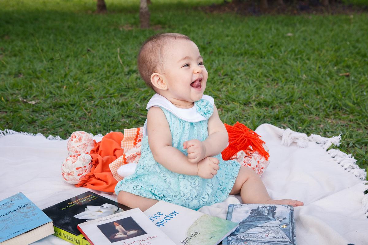 Bebê sentada em um manta no chão em meio a vários livros, gargalhando enquanto olha para sua mãe.