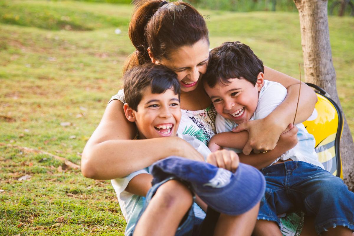 Mãe abraçando dois filhos e fazendo cócegas neles enquanto brincam em um ensaio fotográfico externo de família.