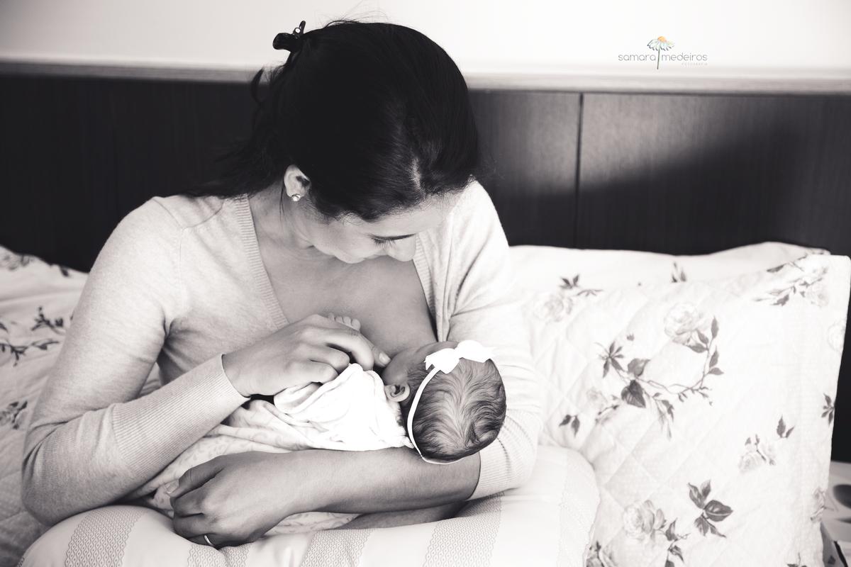 Foto em preto e branco de uma mãe sentada em sua cama amamentando sua filha recém nascida.
