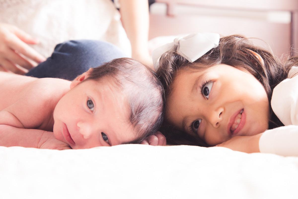 bebê recém nascido e sua irmã mais velha, ambos deitados na cama dos pais de bruços.
