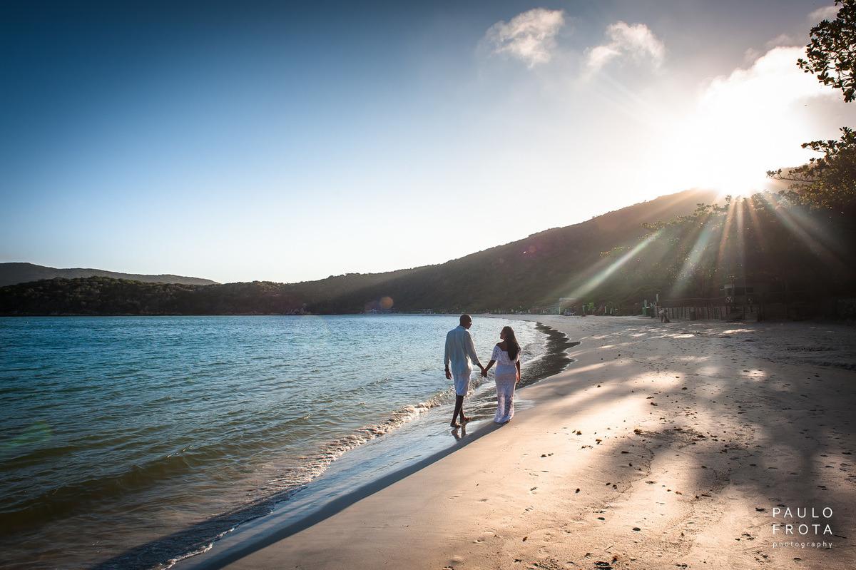 casal andando na praia do forno com sol