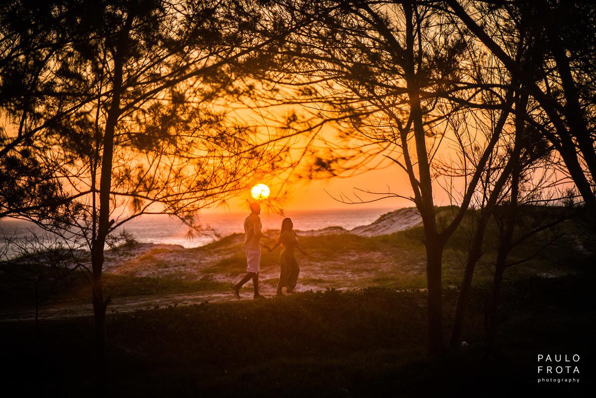 casal andando no gramado, sol atrás