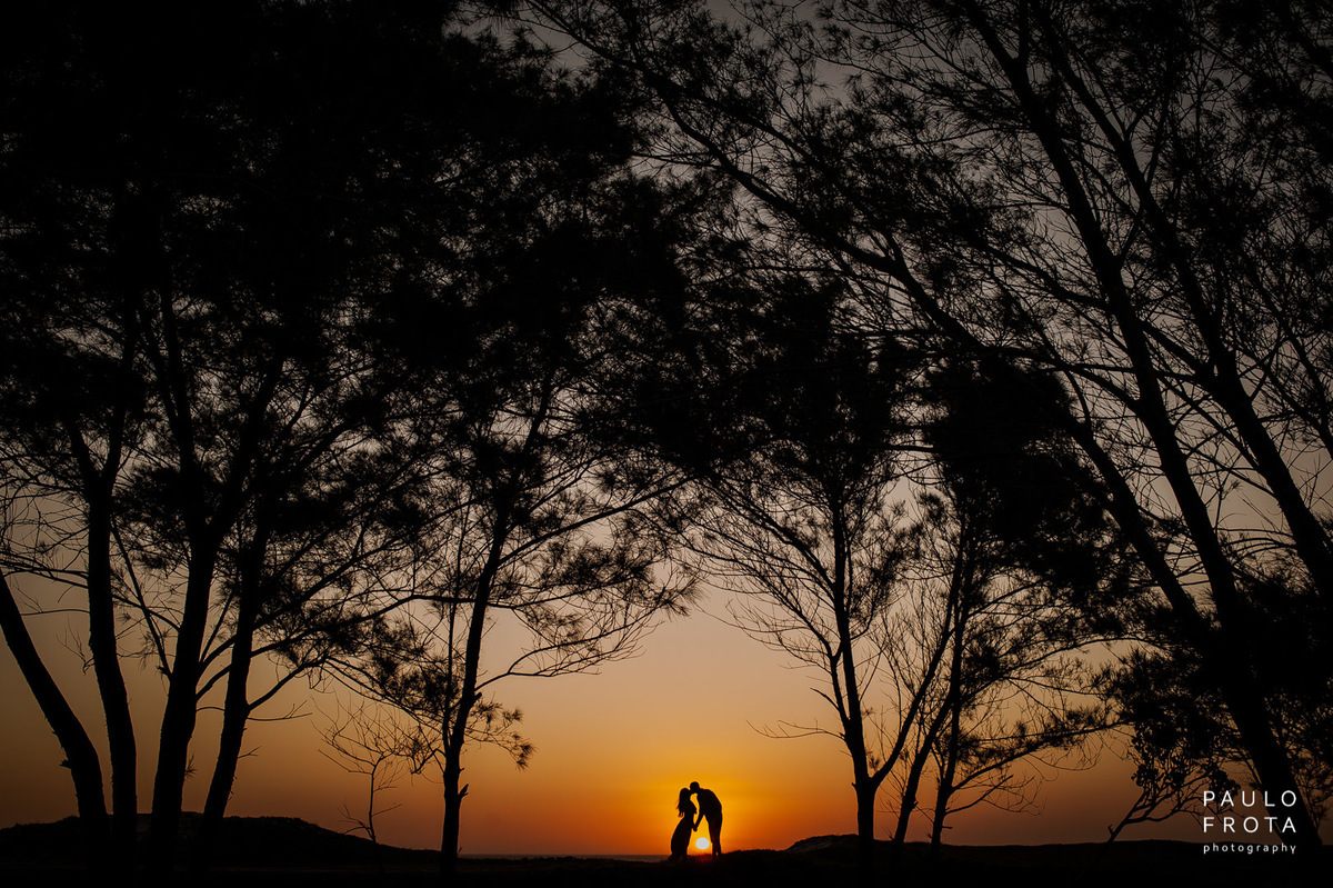 silhueta de casal se beijando, com por do sol entre o casal