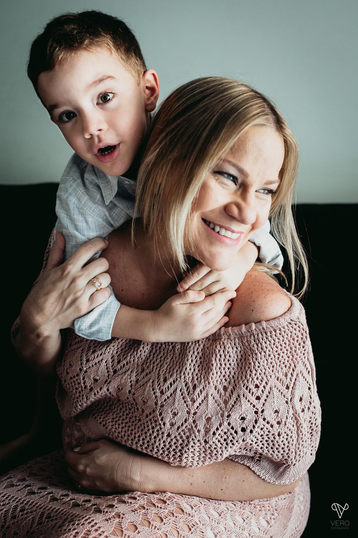 Filho abraça a mãe gestante no sofá da casa