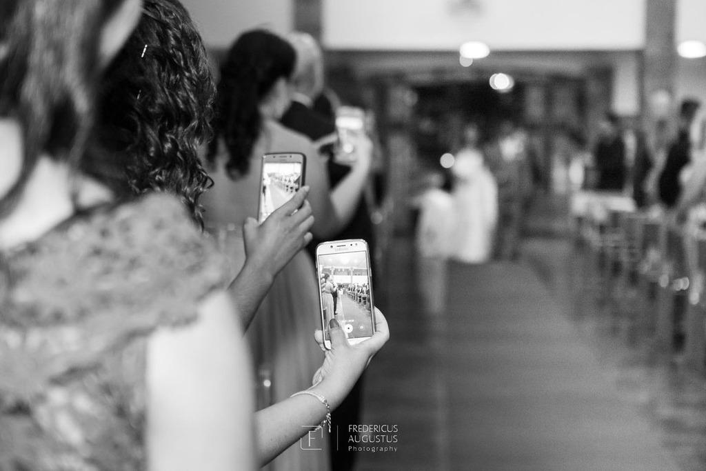 Foto dos celulares fazendo foto da noiva Júnia entrando na  Igreja Nossa Senhora Aparecida