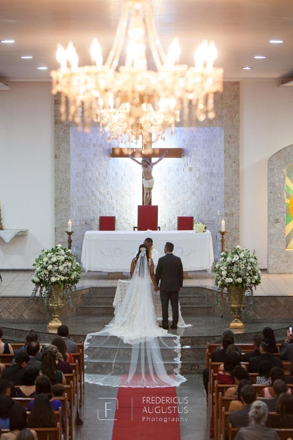 Foto do noivo Felipe e a noiva com o grande véu na  Igreja Nossa Senhora Aparecida