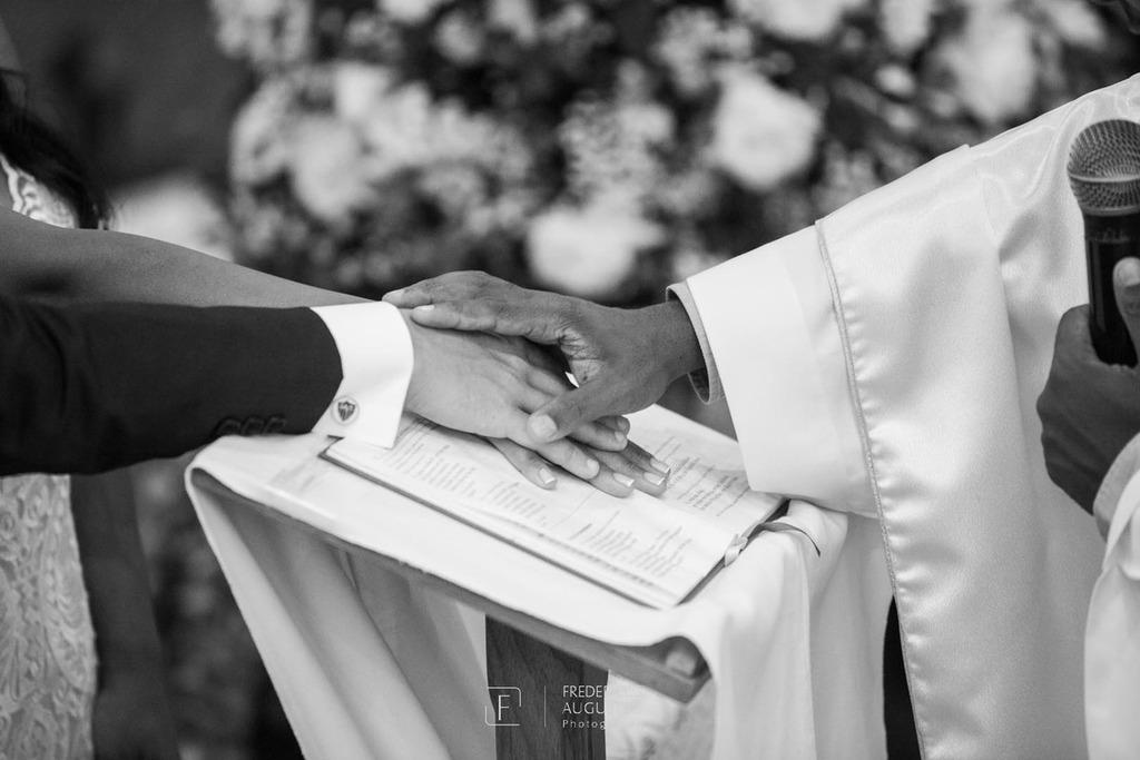As mãos dos noivos Júnia e Felipe com a do Padre Moises em cima da bíblia na  Igreja Nossa Senhora Aparecida