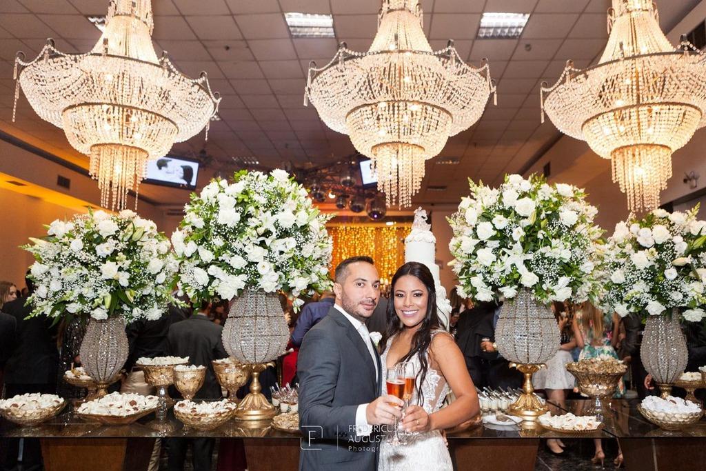 Os noivos Júnia e Felipe brindando na mesa do bolo e doces do Multispace Espaço para Eventos