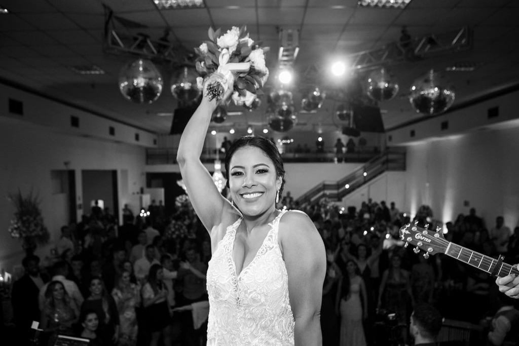A noiva Júnia jogando o buquê no centro do salão do Multispace Espaço para Eventos