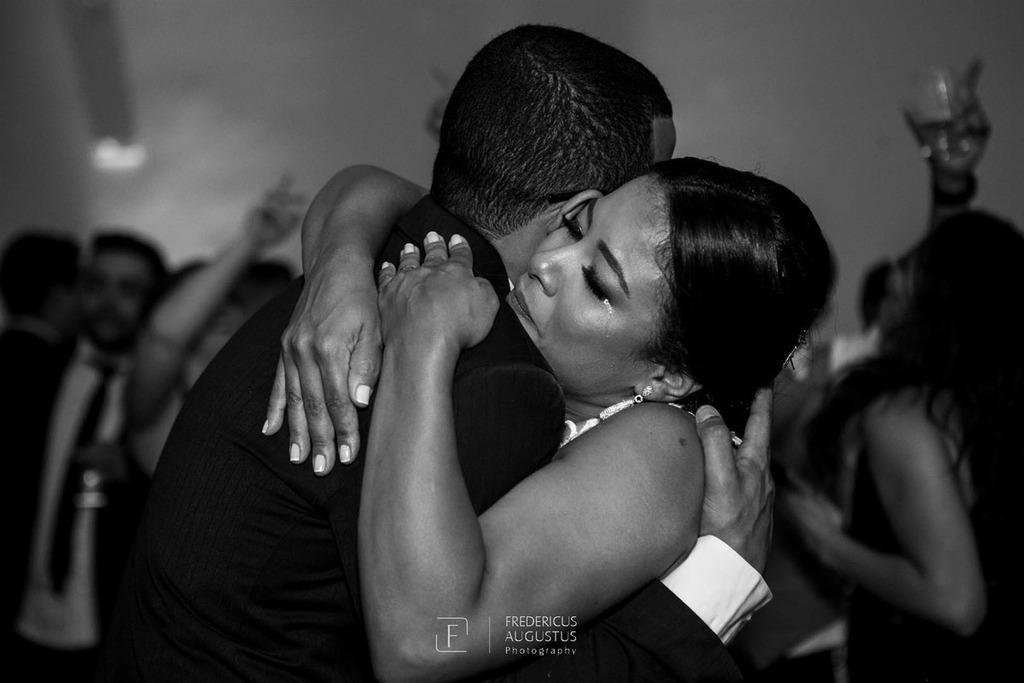 A noiva Júnia emocionada recebendo um grande abraço do seu irmão  no centro do salão do Multispace Espaço para Eventos