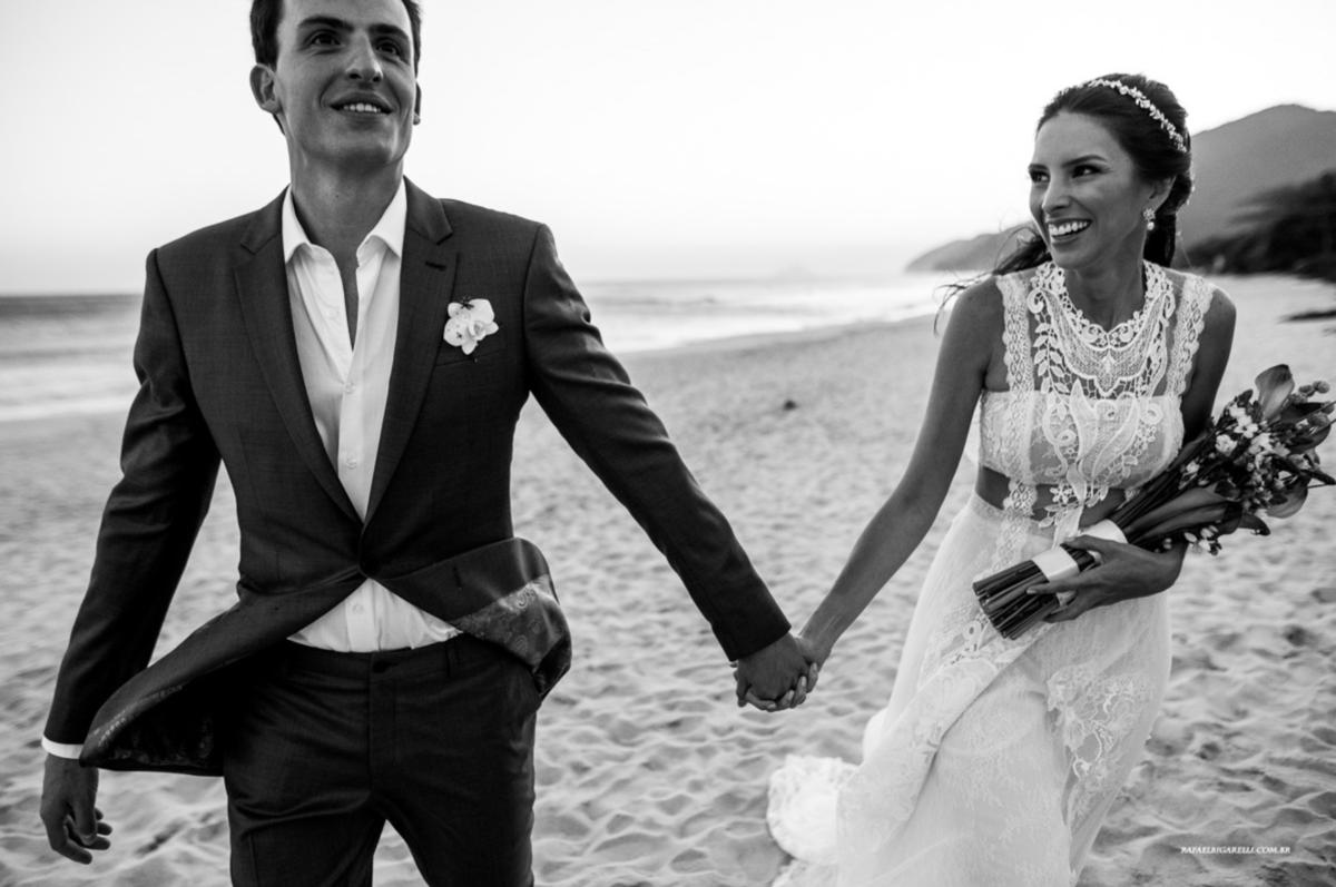 noivos de mãos dadas noiva com vestido de renda segurando o buquê em casamento na praia de maresias litoral norte de são paulo fotografia rafael bigarelli