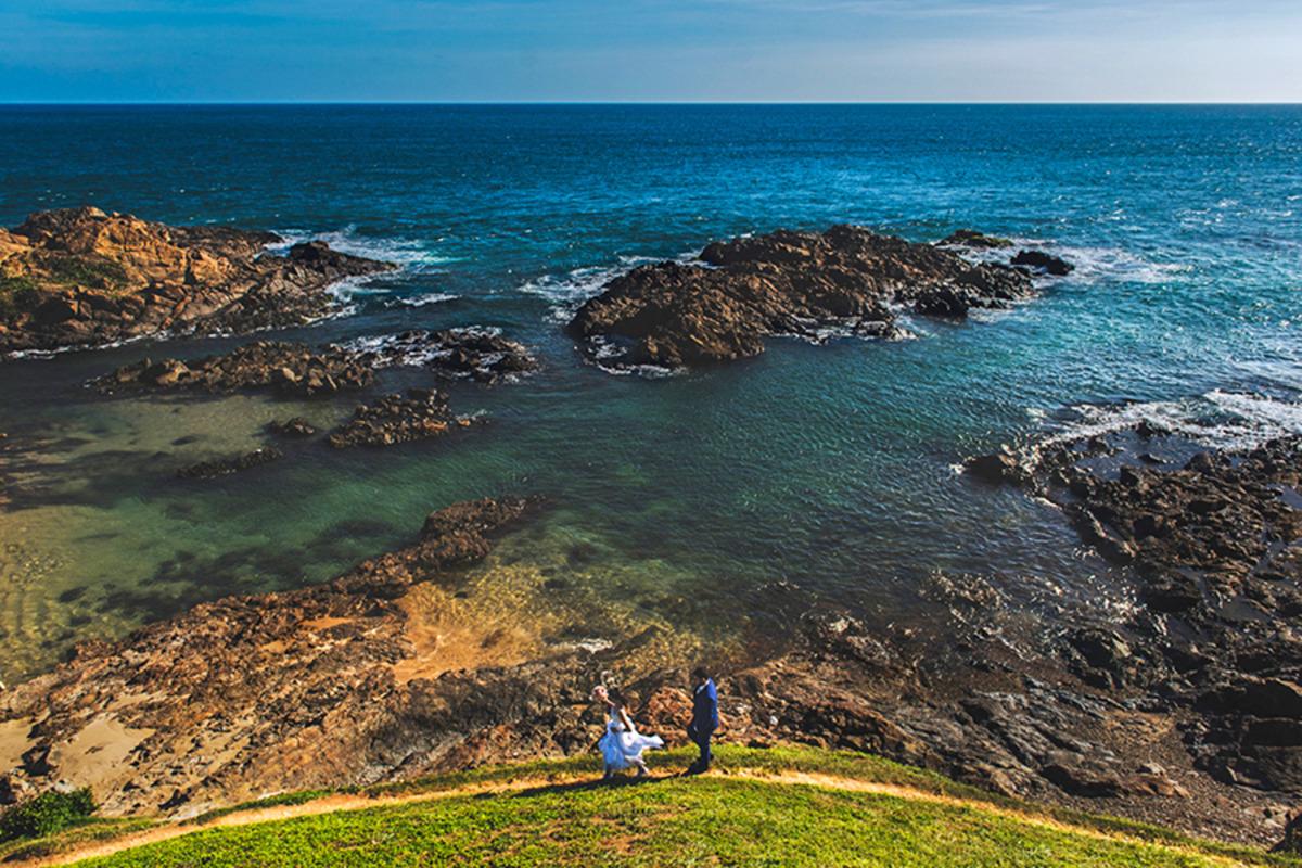 Foto no ensaio de pós casamento na Bahia em Salvador com casal passeando atrás do farol da Barra e com vista pro mar