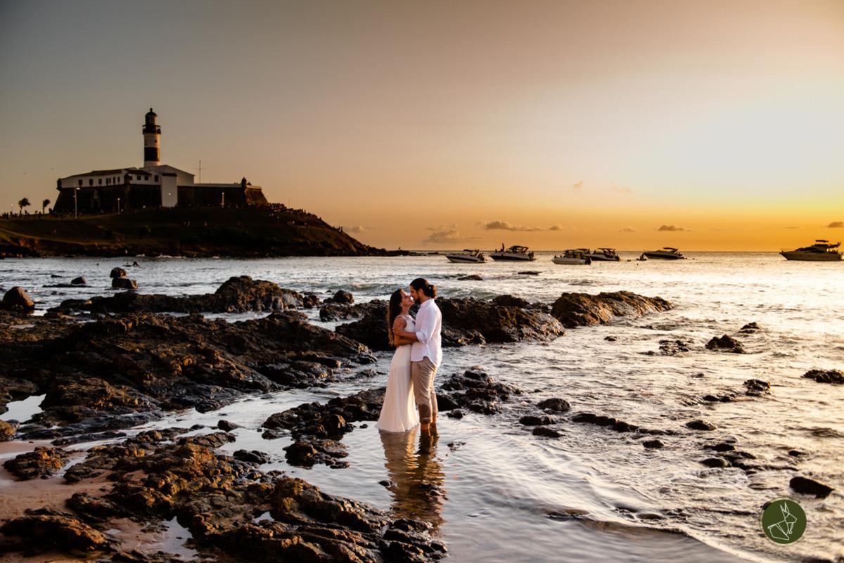 Casal no ensaio de pré casamento dentro do mar por do sol com farol da barra ao fundo em salvador na Bahia