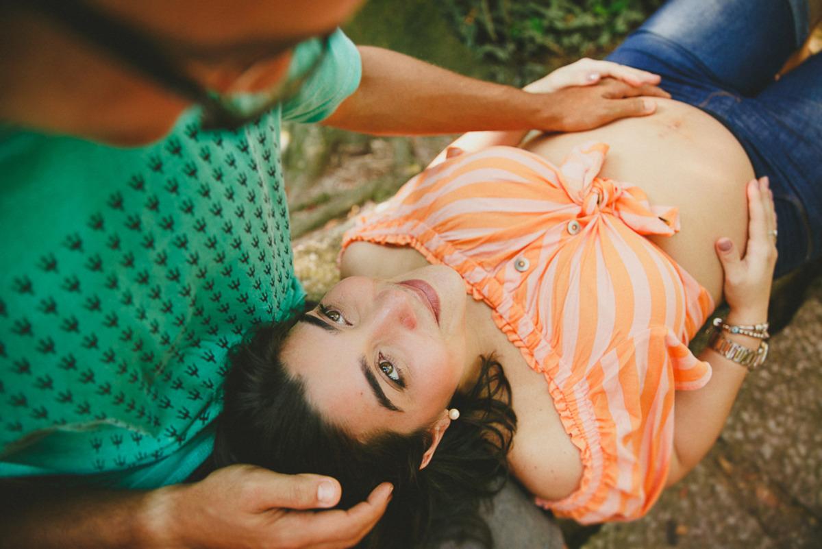 grávida deitada no colo do marido que a olha com ternura à espera do primeiro filho