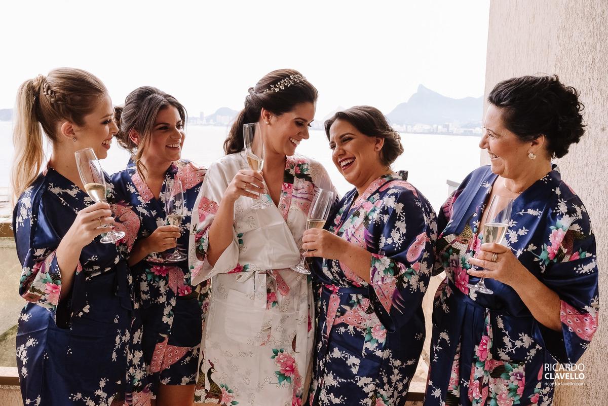 Noiva se arrumando junto com as madrinhas e sua mãe.