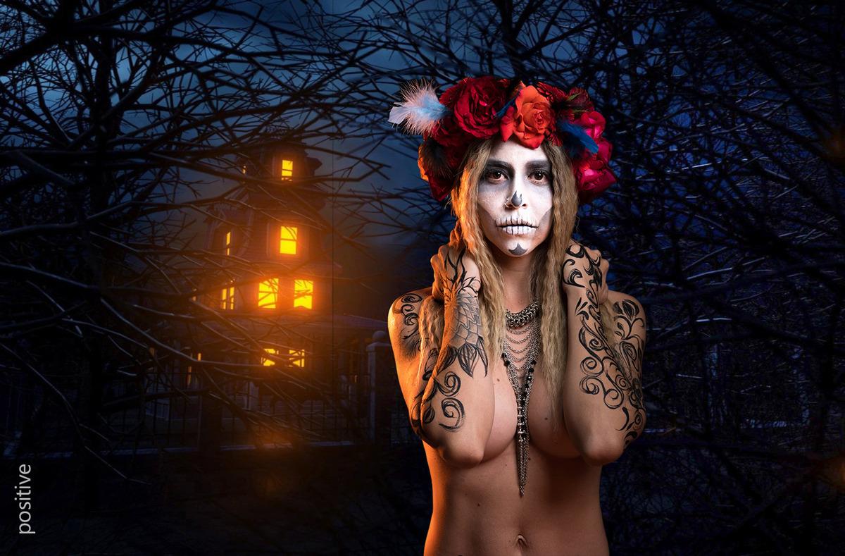 Catrina de noche con casa iluminada detrás de ella