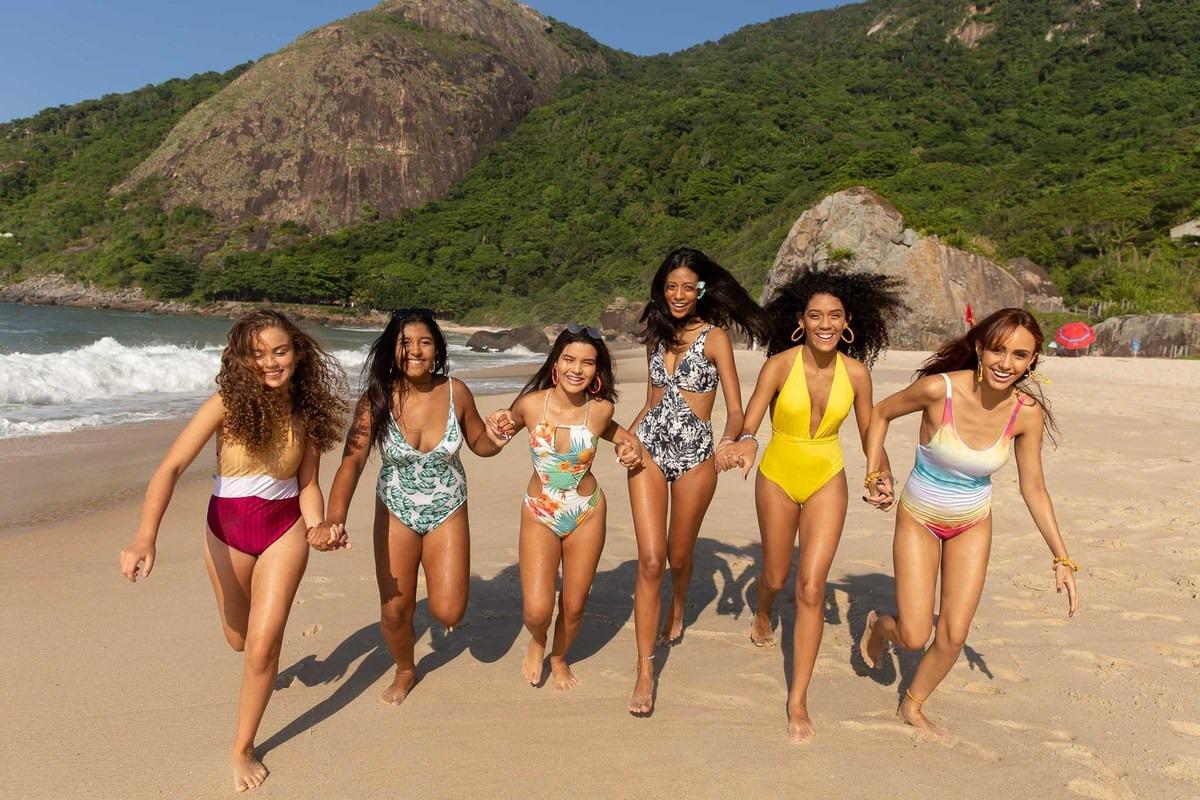 meninas de mãos dadas correndo na areia da praia