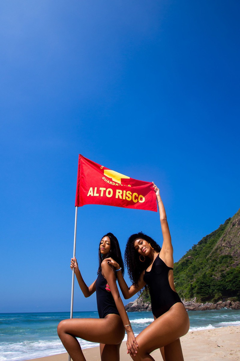 duas meninas segurando a bandeira de alto risco do mar na praia