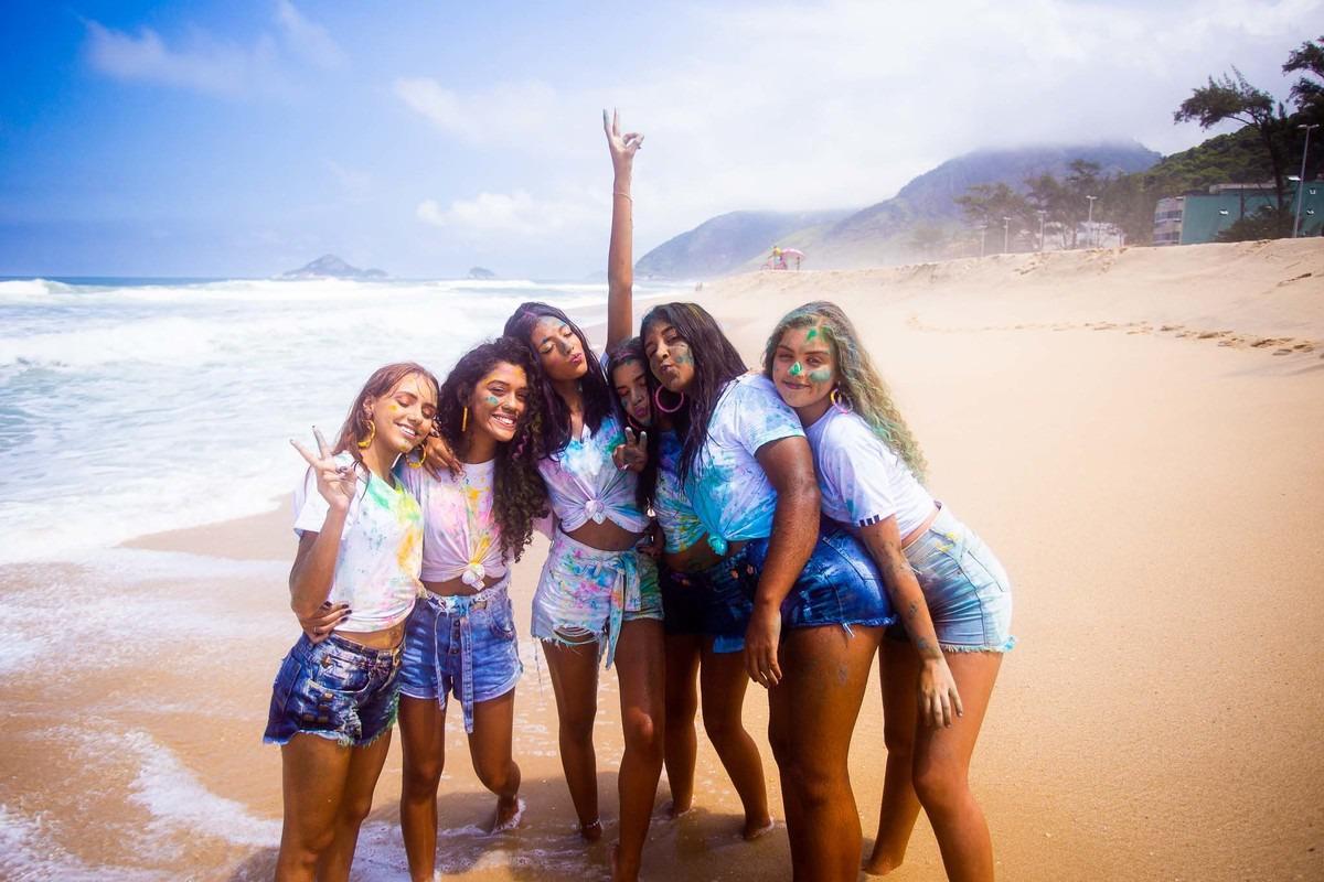 6 amigas posando pra foto na areia da praia da reserva no Rio de Janeiro.